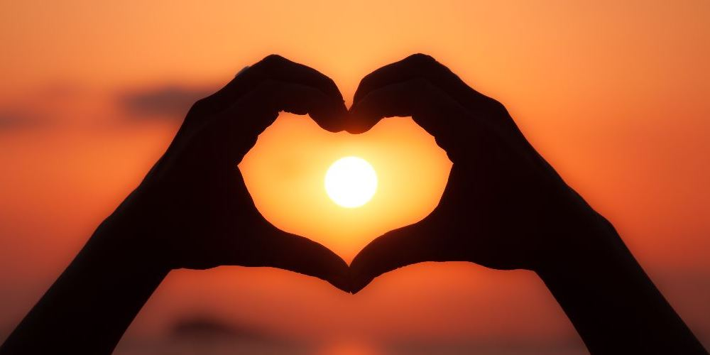 Heart shape, formed by hands, with the setting sun in the middle