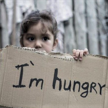 Young girl holding up a sign reading 'I'm hungry'
