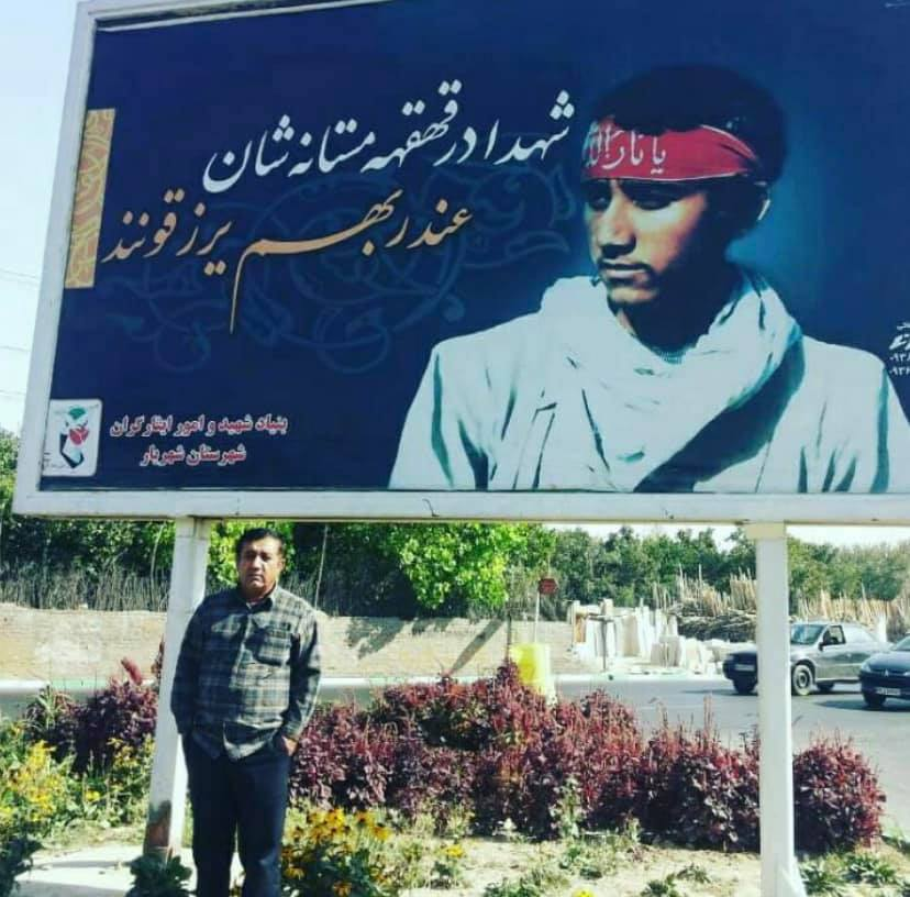 A very alive man, posing in front of a billboard that honors him as a martyr of the Iran-Iraq war