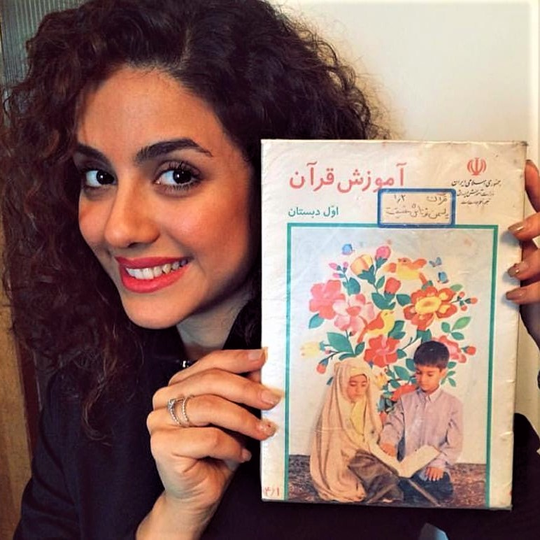 Hijab-less young women shows the cover of an Iranian textbook on which she had appeared with a compulsory hijab